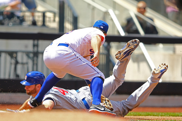 Scott Feldman uses his head as he slides into third base.